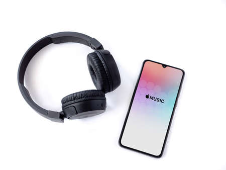 Lod, Israel - July 8, 2020: Black mobile smartphone with Apple Music app launch screen with logo and wireless headphones on a white background. Top view flat lay with copy space.