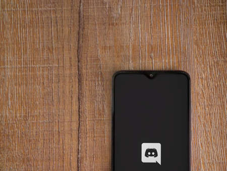 Lod, Israel - July 8, 2020: Discord app launch screen with logo on the display of a black mobile smartphone on wooden background. Top view flat lay with copy space.