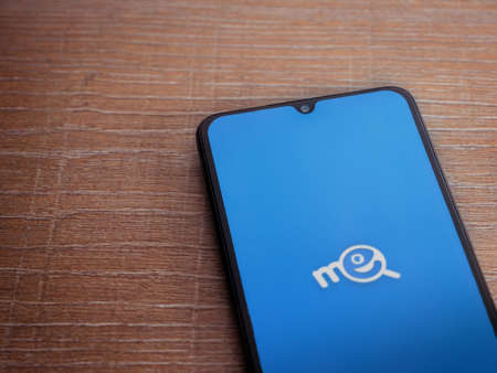 Lod, Israel - July 8, 2020: Me app launch screen with logo on the display of a black mobile smartphone on wooden background. Top view flat lay with copy space.