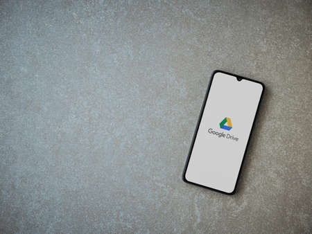 Lod, Israel - July 8, 2020: Google Drive app launch screen with logo on the display of a black mobile smartphone on ceramic stone background. Top view flat lay with copy space.