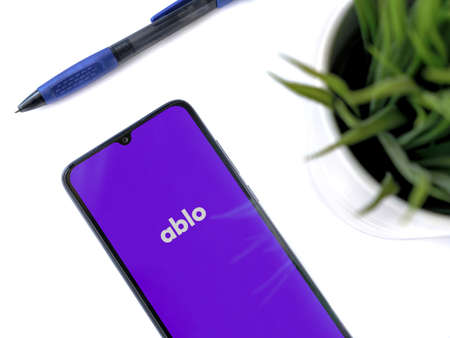 Lod, Israel - July 8, 2020: Modern minimalist office workspace with black mobile smartphone with Ablo app launch screen with logo on white background. Top view flat lay with copy space.