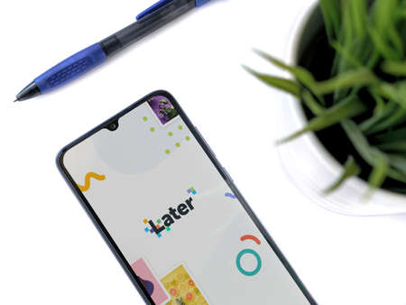 Lod, Israel - July 8, 2020: Modern minimalist office workspace with black mobile smartphone with Later app launch screen with logo on white background. Top view flat lay with copy space.