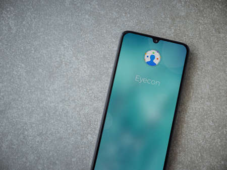 Lod, Israel - July 8, 2020: Eyecon app launch screen with logo on the display of a black mobile smartphone on ceramic stone background. Top view flat lay with copy space.