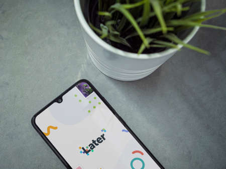 Lod, Israel - July 8, 2020: Modern minimalist office workspace with black mobile smartphone with Later app launch screen with logo on marble background. Top view flat lay with copy space.