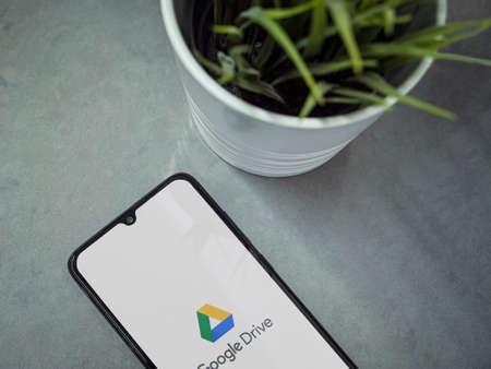 Lod, Israel - July 8, 2020: Modern minimalist office workspace with black mobile smartphone with Google Drive app launch screen with logo on marble background. Top view flat lay with copy space. Editöryel