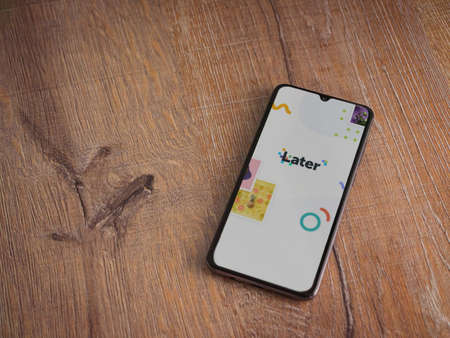 Lod, Israel - July 8, 2020: Later app launch screen with logo on the display of a black mobile smartphone on wooden background. Top view flat lay with copy space.