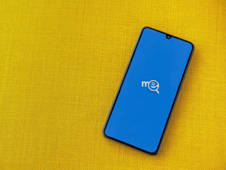 Lod, Israel - July 8, 2020: Me app launch screen with logo on the display of a black mobile smartphone on a yellow fabric background. Top view flat lay with copy space.