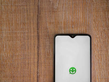 Lod, Israel - July 8, 2020: Scriby app launch screen with logo on the display of a black mobile smartphone on wooden background. Top view flat lay with copy space.