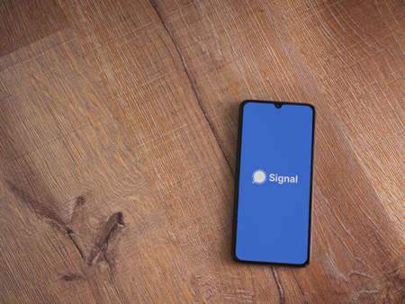 Lod, Israel - July 8, 2020: Signal Private Messenger app launch screen with logo on the display of a black mobile smartphone on wooden background. Top view flat lay with copy space.