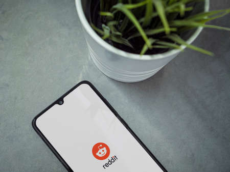 Lod, Israel - July 8, 2020: Modern minimalist office workspace with black mobile smartphone with Reddit app launch screen with logo on marble background. Top view flat lay with copy space.