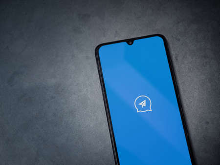 Lod, Israel - July 8, 2020: Quick Message app launch screen with logo on the display of a black mobile smartphone on dark marble stone background. Top view flat lay with copy space.