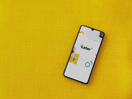 Lod, Israel - July 8, 2020: Later app launch screen with logo on the display of a black mobile smartphone on a yellow fabric background. Top view flat lay with copy space.