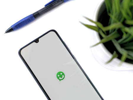 Lod, Israel - July 8, 2020: Modern minimalist office workspace with black mobile smartphone with Scriby app launch screen with logo on white background. Top view flat lay with copy space.