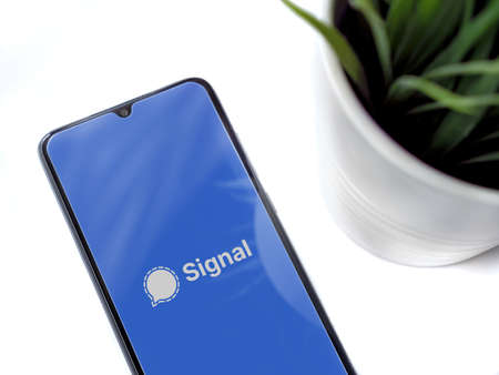Lod, Israel - July 8, 2020: Modern minimalist office workspace with black mobile smartphone with Signal Private Messenger app launch screen with logo on white background. Top view flat lay with copy space.