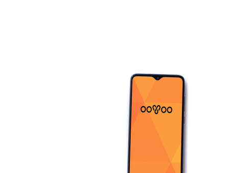 Lod, Israel - July 8, 2020: ooVoo app launch screen with logo on the display of a black mobile smartphone isolated on white background. Top view flat lay with copy space.