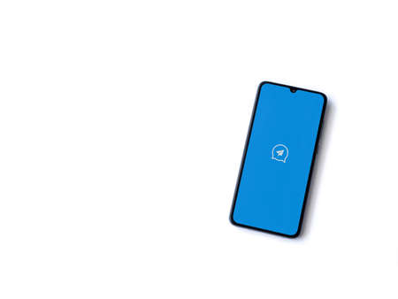 Lod, Israel - July 8, 2020: Quick Message app launch screen with logo on the display of a black mobile smartphone isolated on white background. Top view flat lay with copy space.