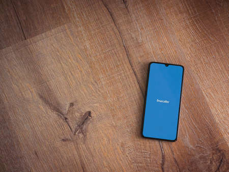 Lod, Israel - July 8, 2020: Truecaller app launch screen with logo on the display of a black mobile smartphone on wooden background. Top view flat lay with copy space. Editöryel