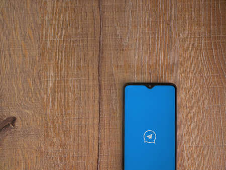 Lod, Israel - July 8, 2020: Quick Message app launch screen with logo on the display of a black mobile smartphone on wooden background. Top view flat lay with copy space.