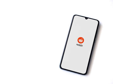 Lod, Israel - July 8, 2020: Reddit app launch screen with logo on the display of a black mobile smartphone isolated on white background. Top view flat lay with copy space.