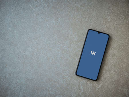 Lod, Israel - July 8, 2020: VK app launch screen with logo on the display of a black mobile smartphone on ceramic stone background. Top view flat lay with copy space.