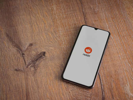 Lod, Israel - July 8, 2020: Reddit app launch screen with logo on the display of a black mobile smartphone on wooden background. Top view flat lay with copy space.