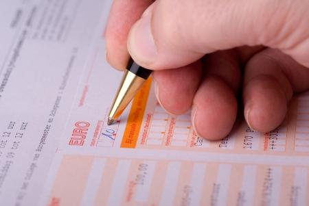bank overschrijving: Hand van een man invullen van een overschrijvingsformulier Stockfoto