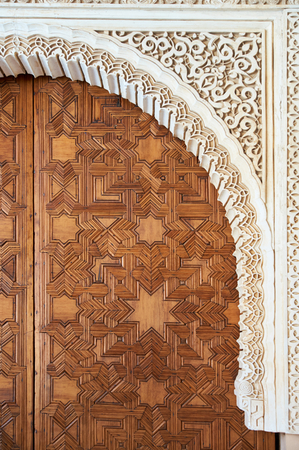 marqueteria: Detalle de talla de madera y escultura de piedra. Gran puerta de estilo árabe en madera preciosa. Alhambra, Granada, España