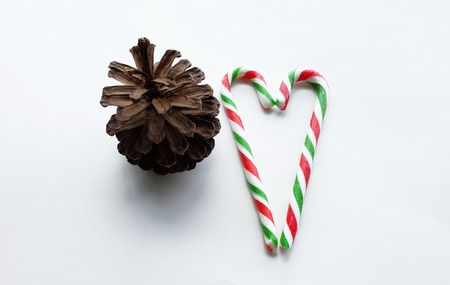 cone shaped: Christmas candy cane with pine cone and heart shaped on white background
