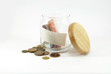 Banknote and coins in glass jar with copy sapce on the jar: white background