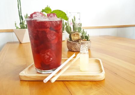 Refreshment iced roselle drink on wooden plate and table with mint leaf