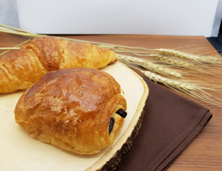 Plain and Chocolate croissant on wooden board and rustic background Foto de archivo