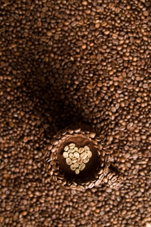 coffe beans: Coffe mug made of coffe beans standing on the surface of coffee, filled with raw, heart shaped coffee beans