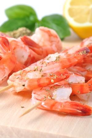 Shrimps, olives, lemon, and basil on board isolated on white background photo