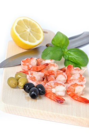 Shrimps, olives, lemon, and basil on board isolated on white background photo