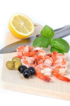 Shrimps, olives, lemon, and basil on board isolated on white background