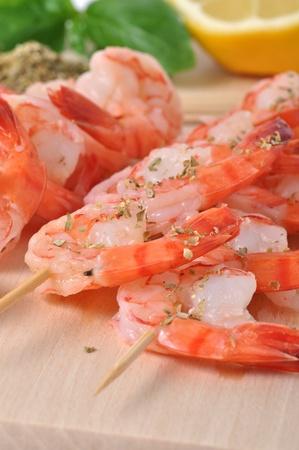 Shrimps, lemon, and basil on board isolated on white background Stock Photo