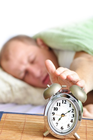 sat: A man is sleeping with an alarm clock in front