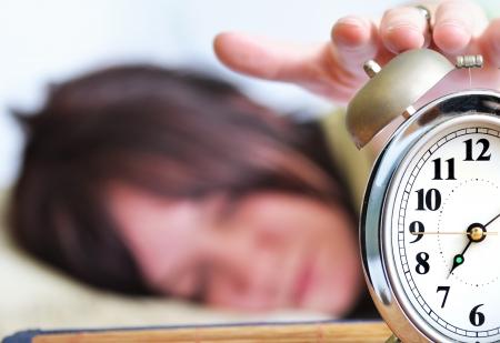 despertarse: Una mujer est� durmiendo con un reloj de alarma en el frente