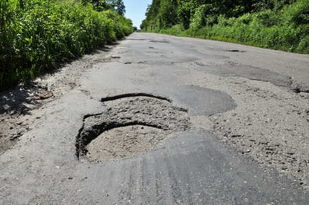 pothole: A big hole on damage road in Poland.