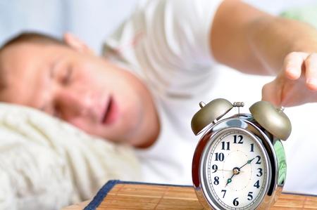 dia y noche: Un hombre est� durmiendo con un reloj de alarma frente
