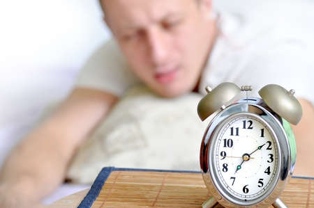 A man is sleeping with an alarm clock in front Stock Photo - 9030114