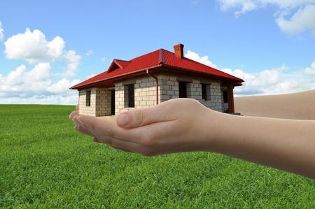 Casa en las manos con el campo verde y el cielo azul en el fondo