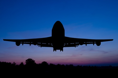 Silhouette of the big plane starting on a sunset background.  photo