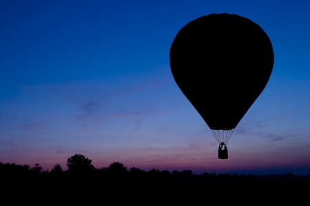 Silhouette of the hot air balloon on a sunset background.  photo