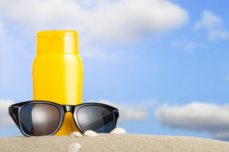 sunnies: Tube with sun protection and sunglasses on beach and blue sky in background