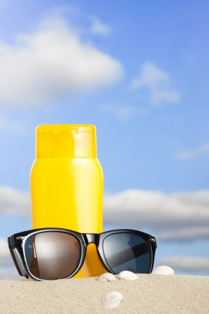 Tube with sun protection and sunglasses on beach and blue sky in background photo