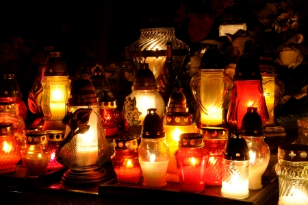 all saints  day: Group of candles on grave during All Saints Day in Poland