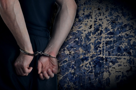 criminals: Men with handcuffs and grunge wall in background Stock Photo