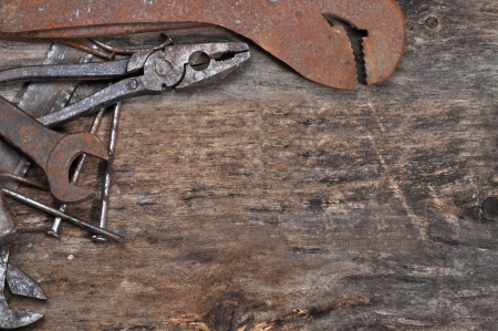 rusty nail: Rusty tools on old wood background