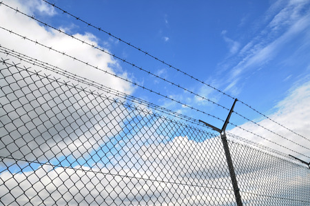 wired fence and blue sky in background photo